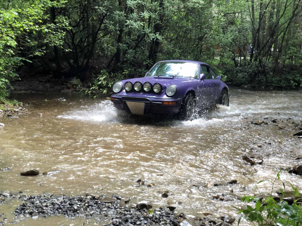 Custom Built 1978 Porsche 911 SC with Lilac exterior and Pascha interio driving through the water in the woods