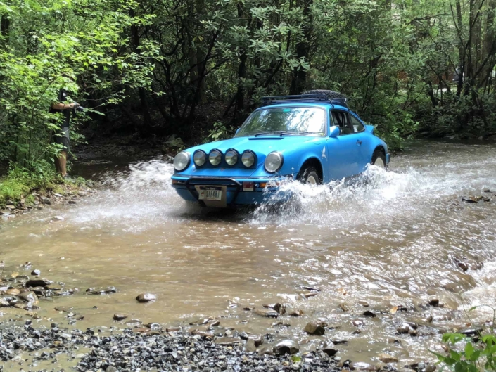 Custom Built 1980 Porsche 911 SC in Riviera Blue driving through the water in the woods