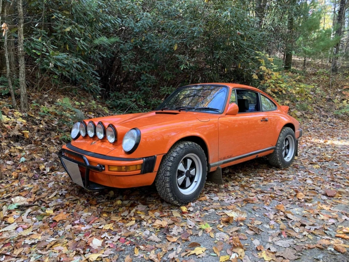 Custom built 1987 Porsche 911 Carrera with Continental Orange exterior and VW tartan interior parked in the fall folliage