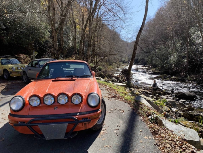 Custom built 1987 Porsche 911 Carrera with Continental Orange exterior and VW tartan interior parked in the woods