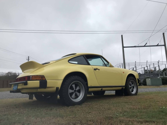 3/4 side view of a Custom Built 1984 Porsche 911 Carrera Euro with Hellgelb Exterior and Mercedes Tartan Interior on a cloudy day