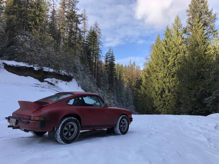Custom Built 1987 Porsche 911 Carrera with Cherry Red exterior and VW retro interior driving through the snow