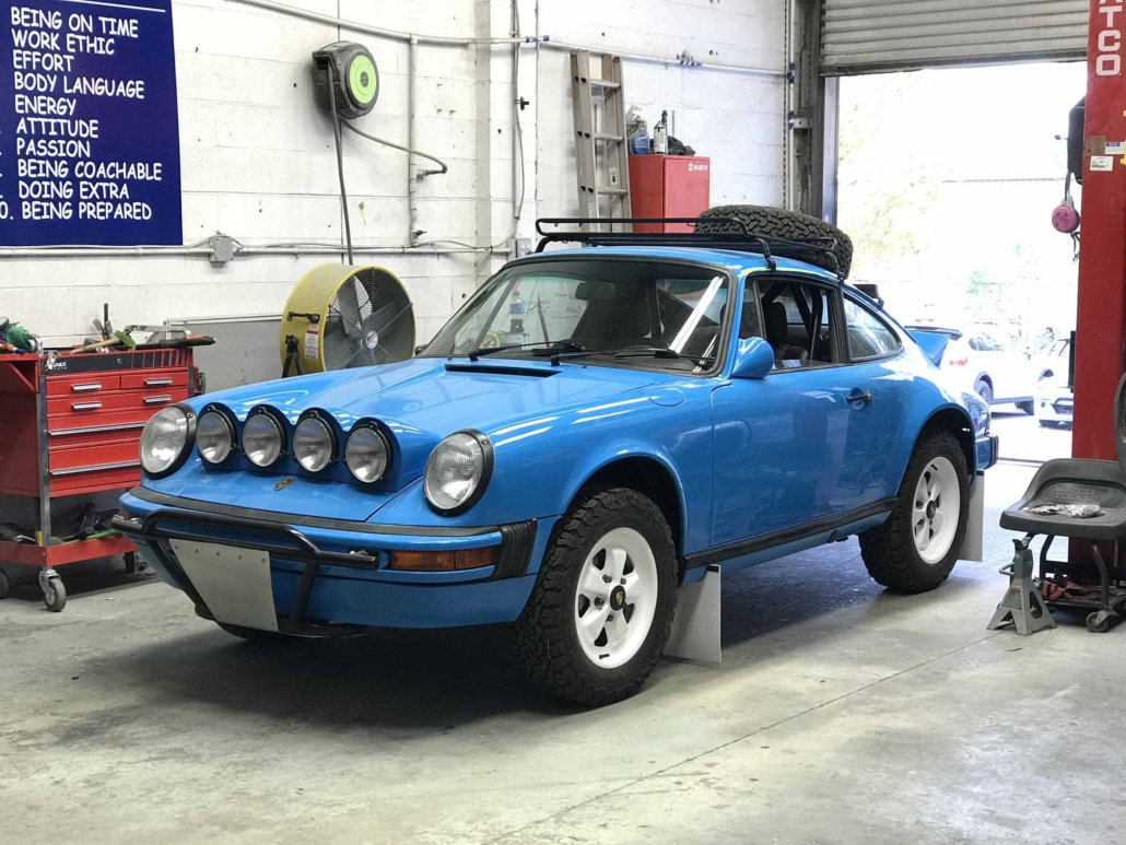 Custom Built 1980 Porsche 911 SC in Riviera Blue with blue and brown basket weave interior parked in a mechanic shop
