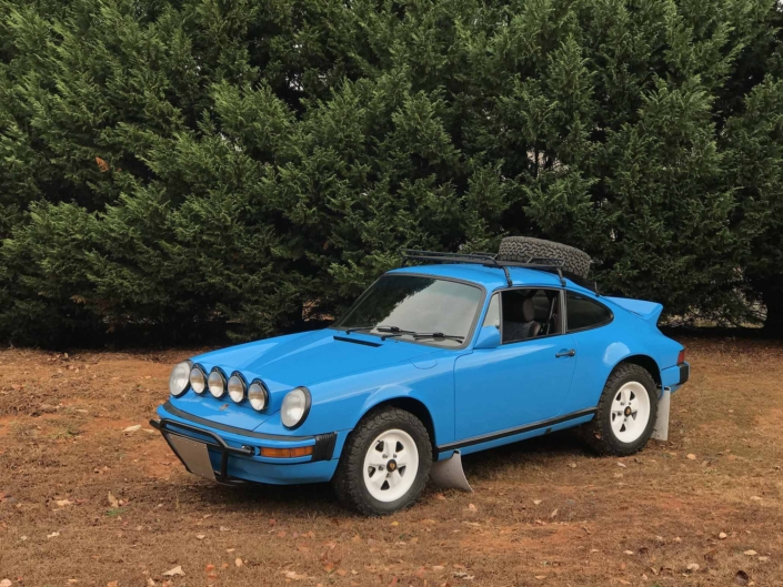Custom Built 1980 Porsche 911 SC in Riviera Blue with blue and brown basket weave interior parked on dirt with the woods in the background