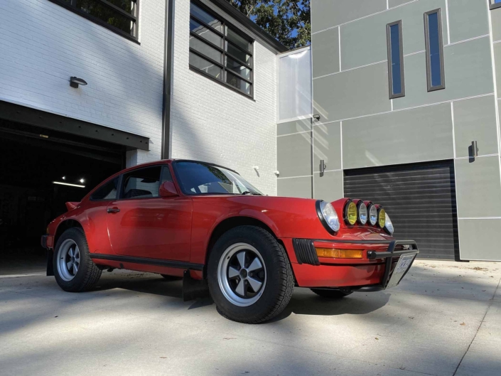 Custom Built 1987 Porsche 911 Carrera with Cherry Red exterior and VW retro interior parked in front of a modern garage
