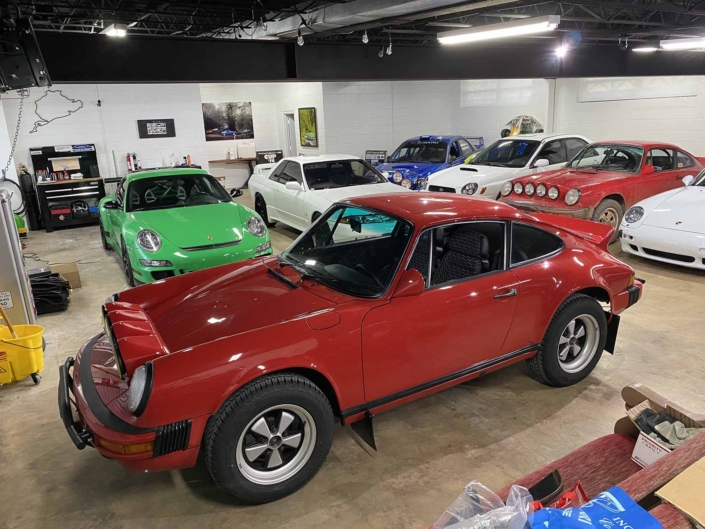 Custom Built 1987 Porsche 911 Carrera with Cherry Red exterior and VW retro interior parked in a garage