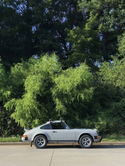 side view of a Custom Built 1986 Porsche 911 Carrera with Fashion Grey Exterior and Lancia Fabric Interior in the woods