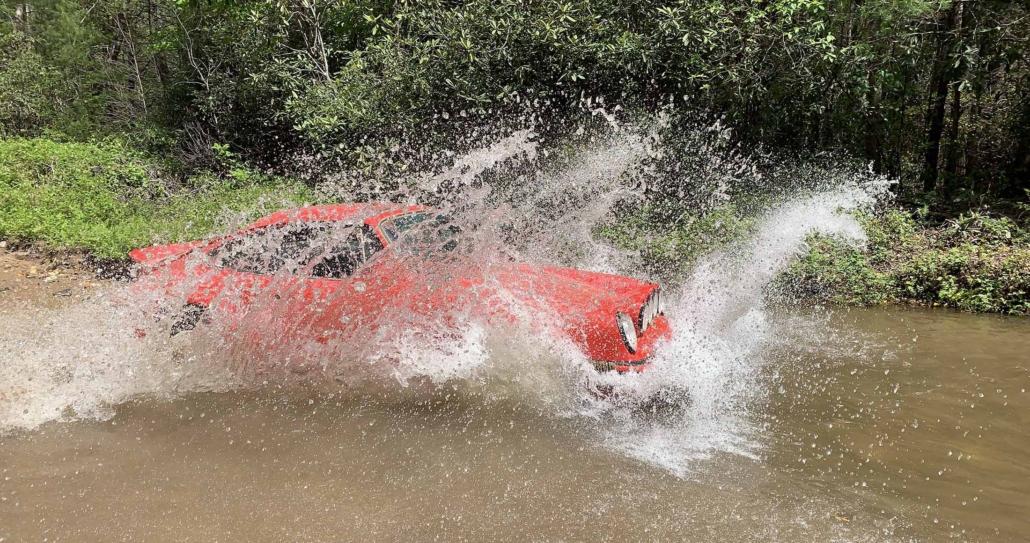 Custom Built 1981 Guards Red Porsche 911 SC driving through water