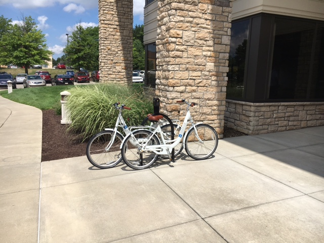 Two bicycles parked in front of a stone-walled building