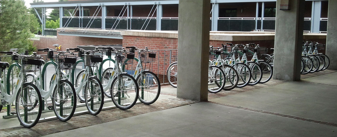 Three sets of bicycle parked in a covered area