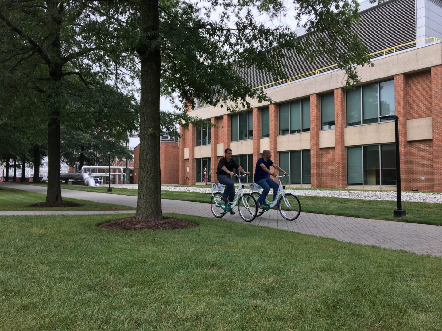 Two men riding a bicycling on campus grounds