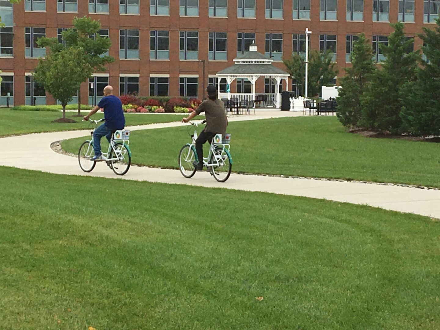 Two people riding a bike along a curved pathway