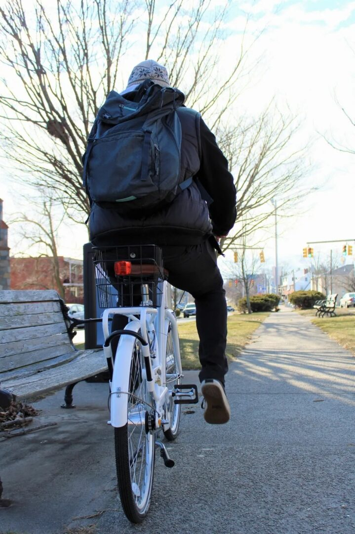 A person with a backpack riding a bike