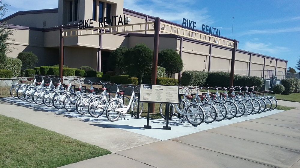 An array of bicycles with a bike rental signage