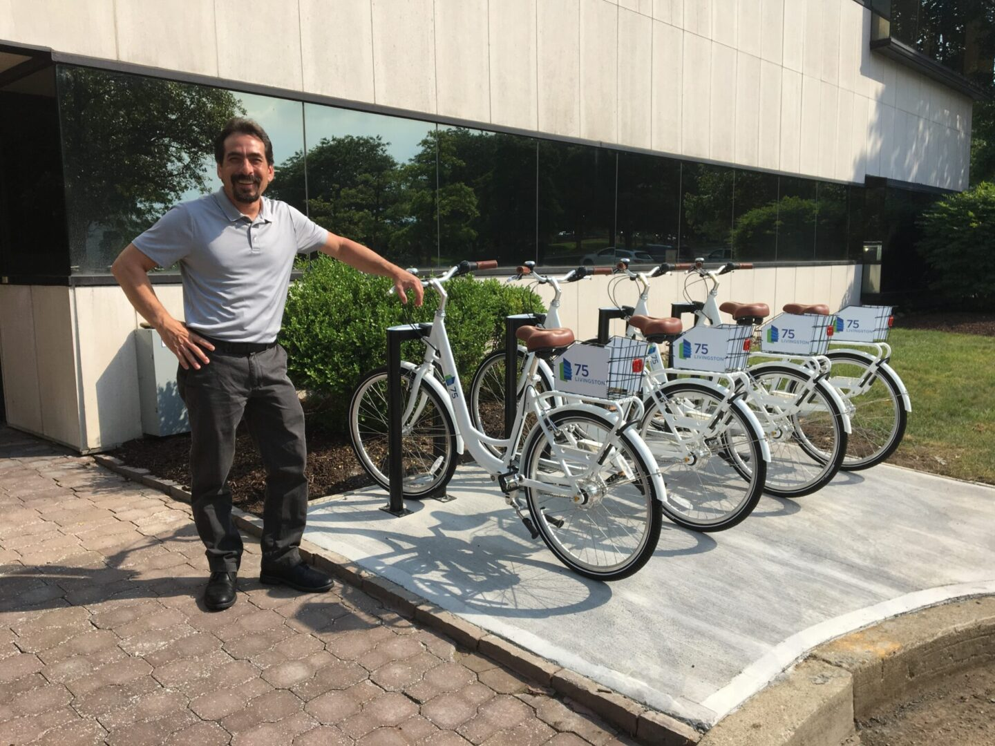 A man smiling in beside a set of bicycles