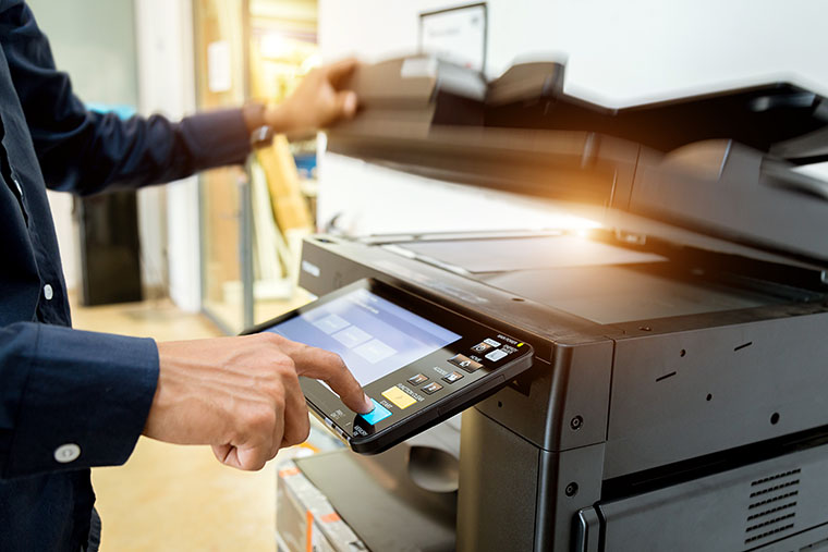 Man using a copier to make bulk copies