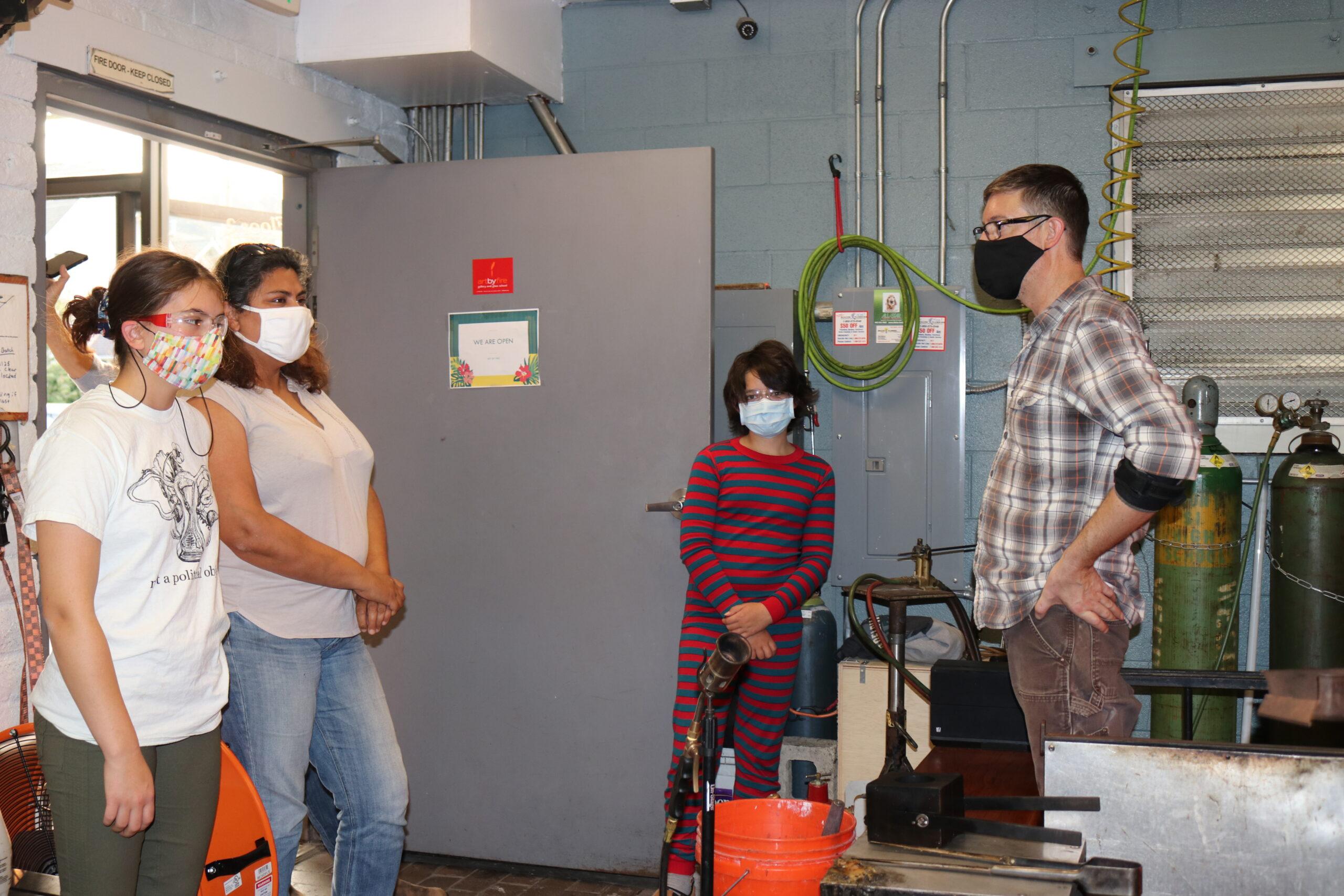 4 people in glass blowing studio