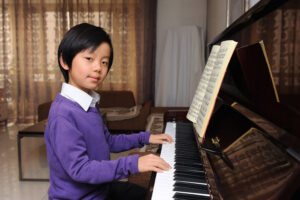 Young Chinese Boy taking Piano lessons in his home