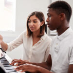 Piano Teacher with student taking piano lessons