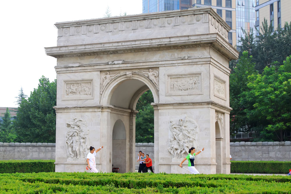 shutterstock_137515010 Hebei, A lady in practicing Swordsmanship in front of the Triumphal Arch in the Stone Door park