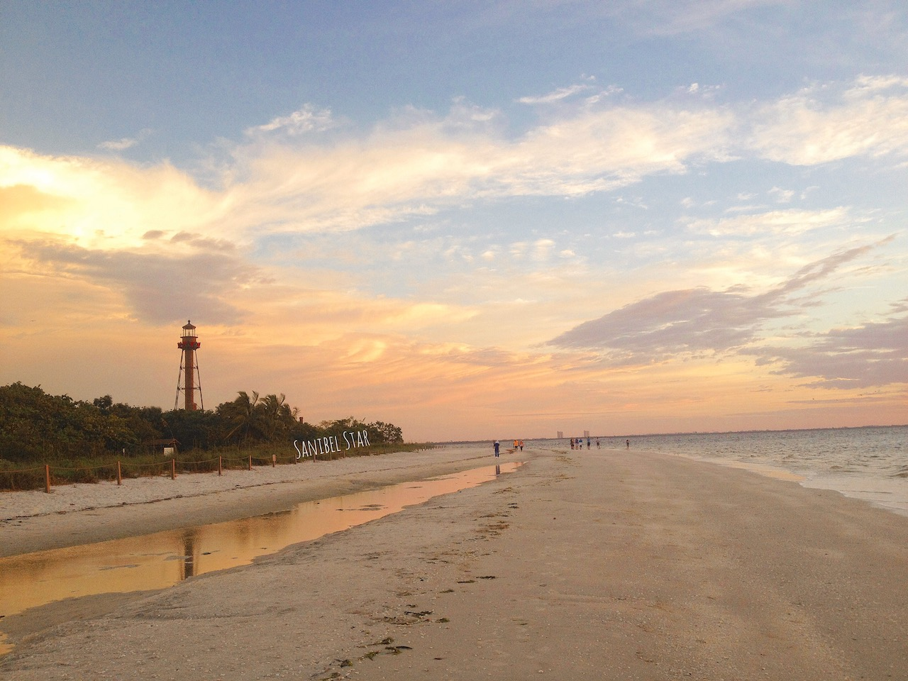 three tier, brown lighthouse on beautiful pale suunset beach
