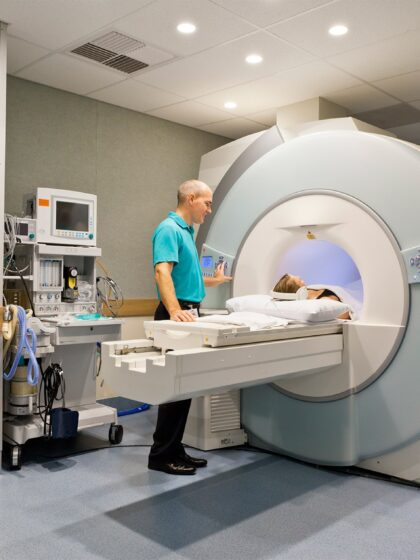 image of a patient going into a ct scan machine with a tech operator beside the patient