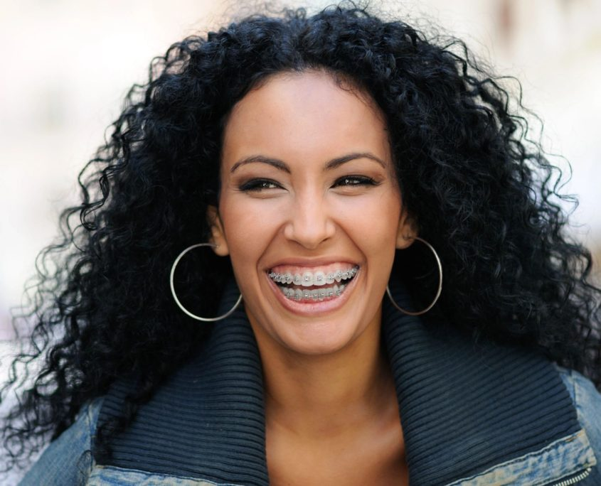 woman curly hair braces smiling