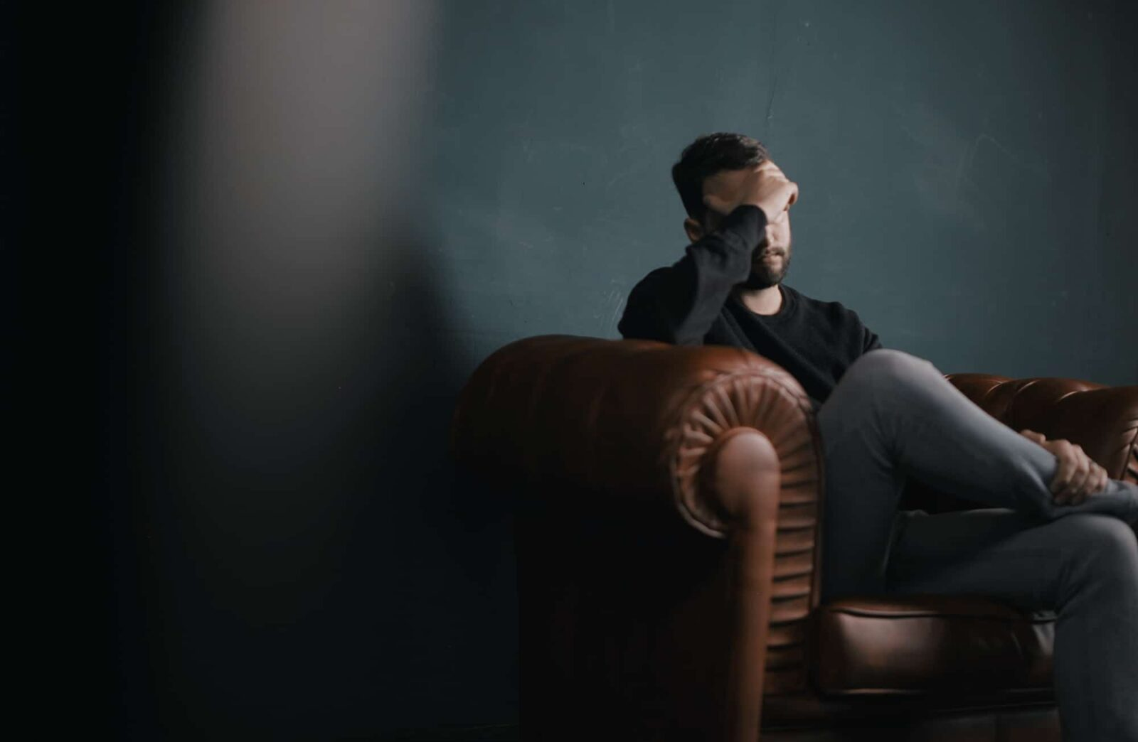 man-sitting-on-brown-couch-against-wall