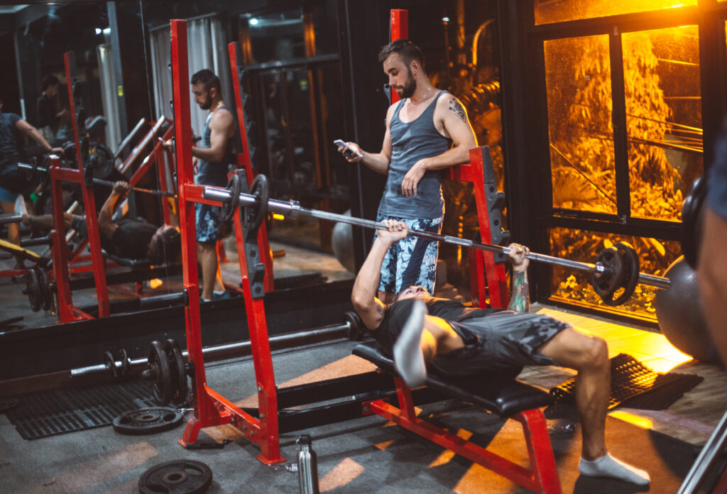 Guy on phone instead of spotting bench press lifter