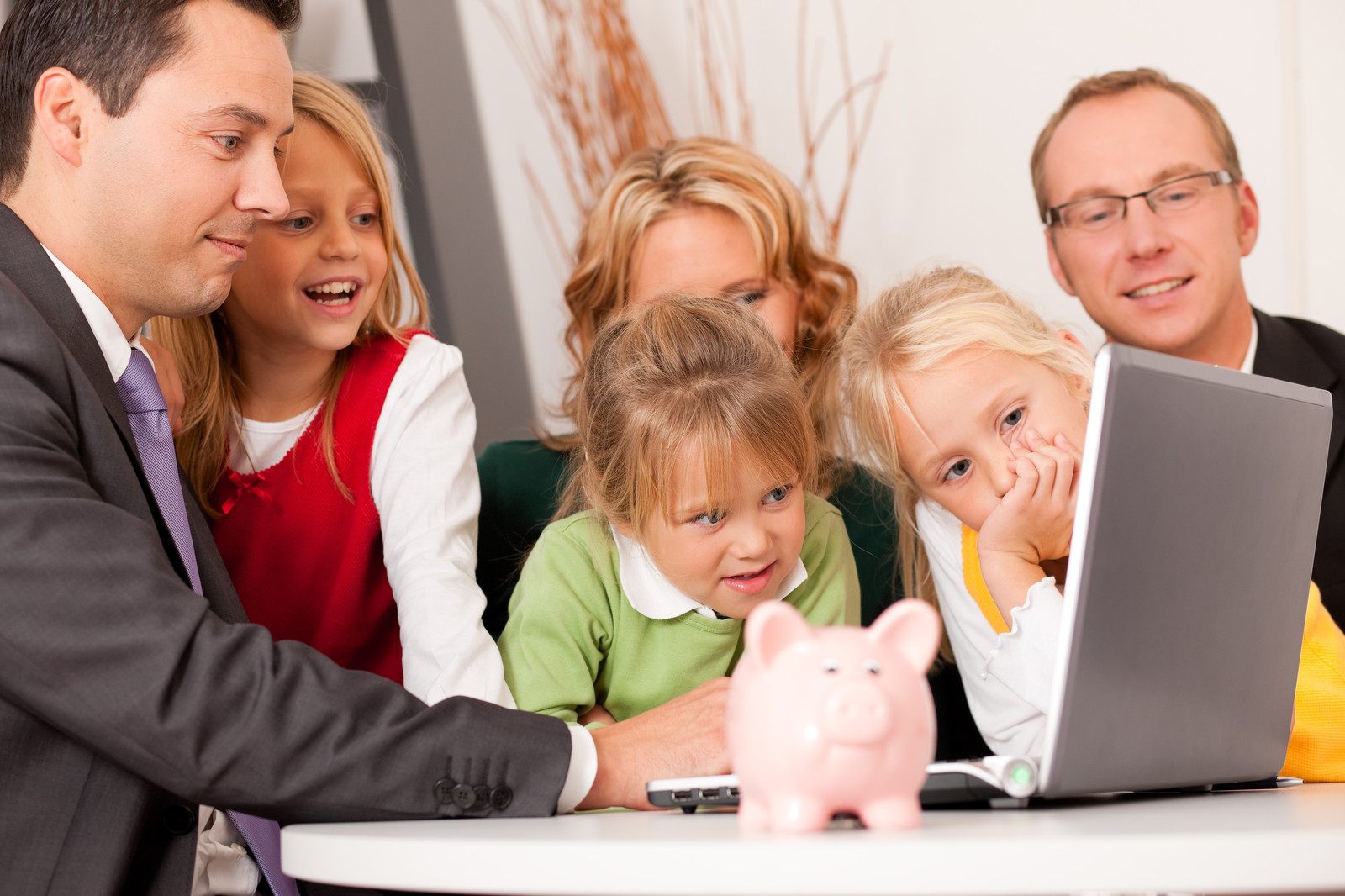 Family around a computer with a piggy bank