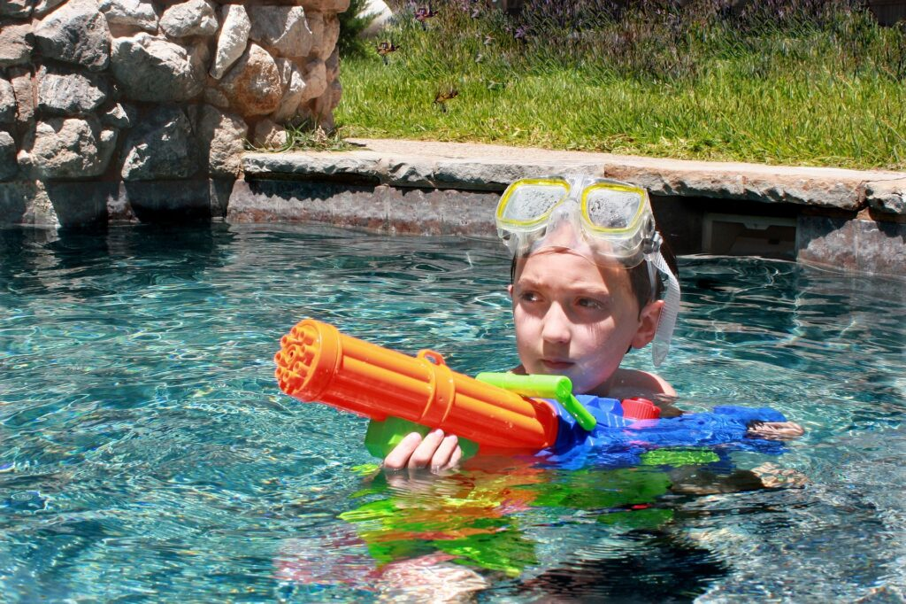 Kid in the pool with super soakers