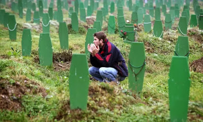 Photo courtesy guardian.co.uk: man praying at the gravesites of Srebenica