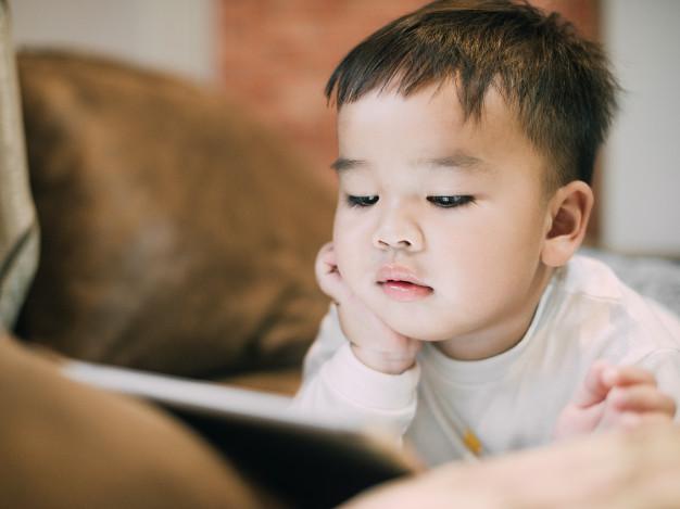Na foto uma criança com um iPad