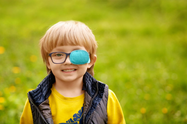 Na foto uma criança usando tampão (oclusão) no olho esquerdo