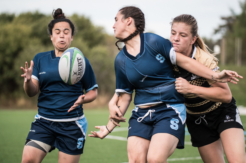 A woman catching a rugby ball in need of massage therapy.