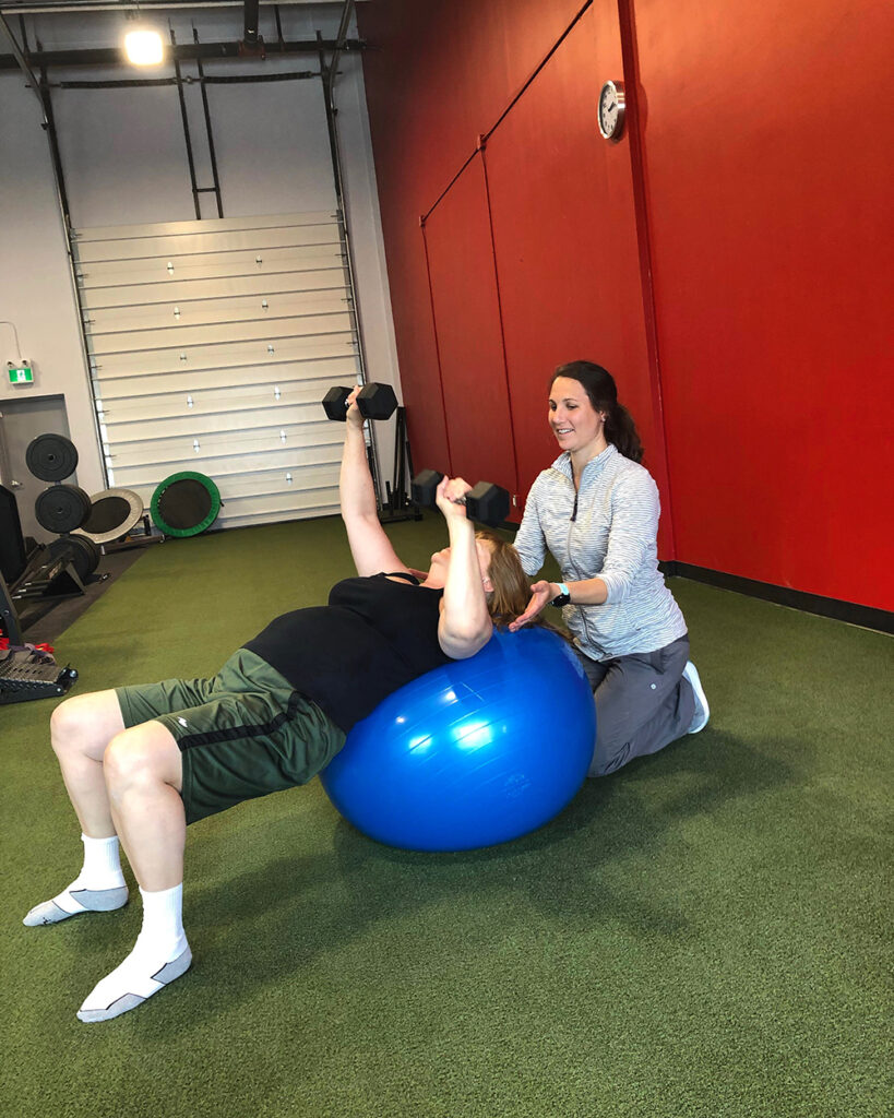 A woman pressing dumbbells on an exercise ball doing physiotherapy.