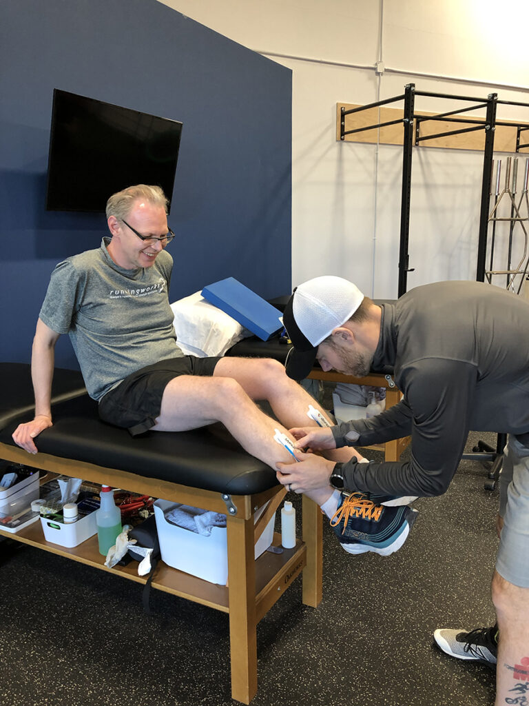 Athletic therapy on a man's shins.