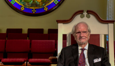 Dr. Jimmy Latimer sitting in front of stained glass