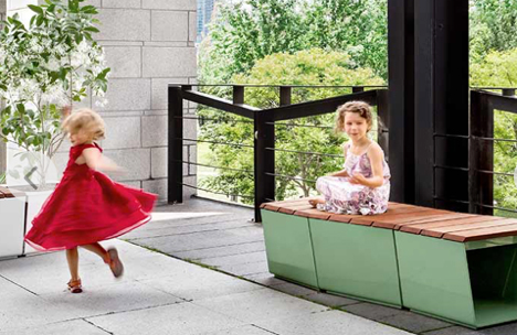 Girl in red dress twirling and a girl in white dress sitting on bench