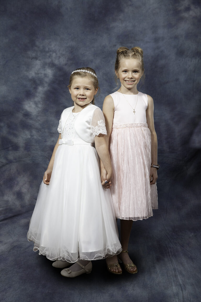 Young children in dresses smiling for the camera