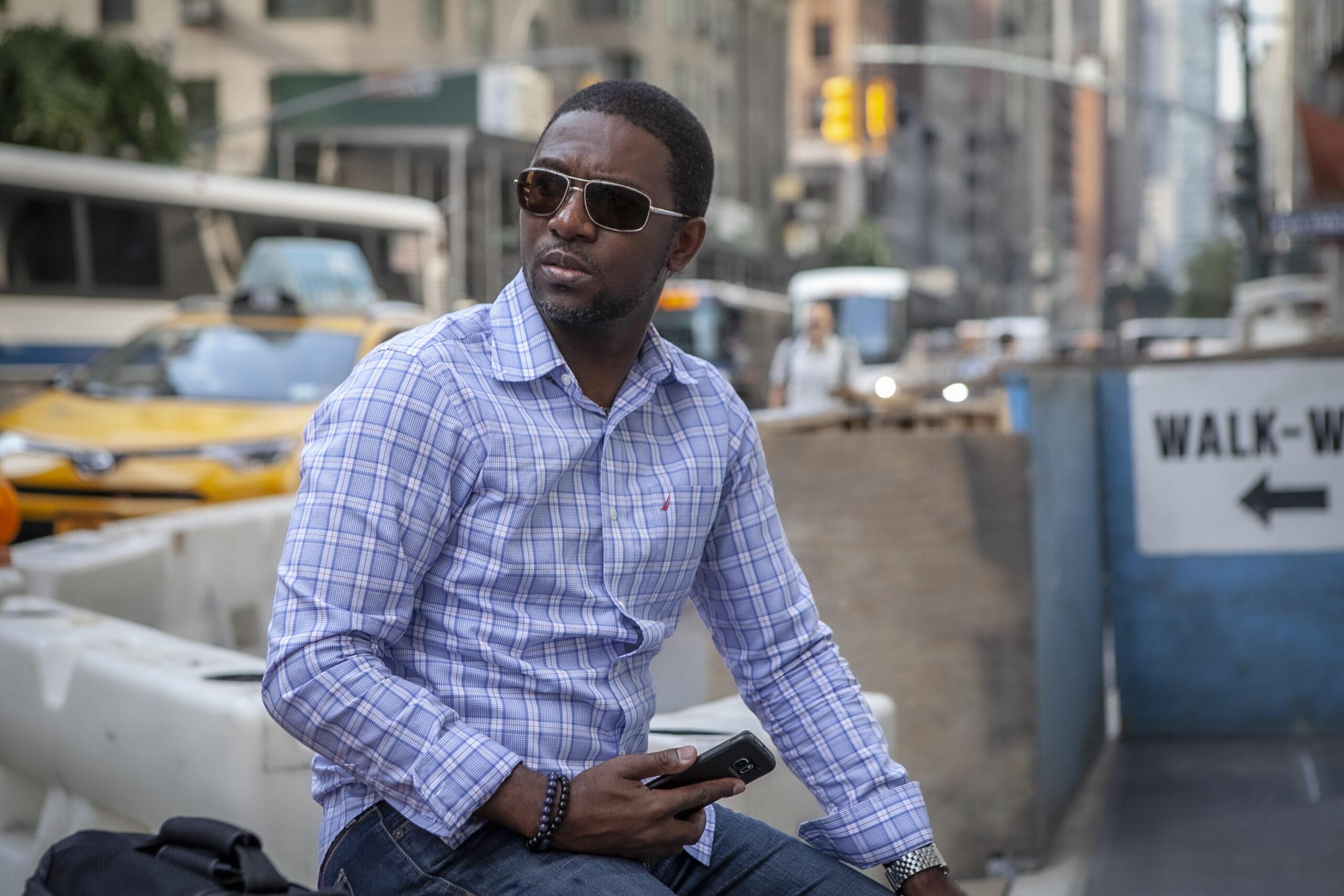 Photographer sitting on a street corner in Manhattan