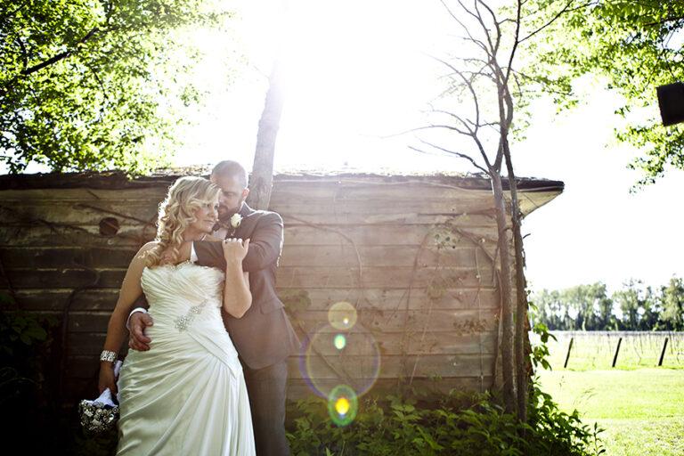 Groom hugging his Bride near a wood house
