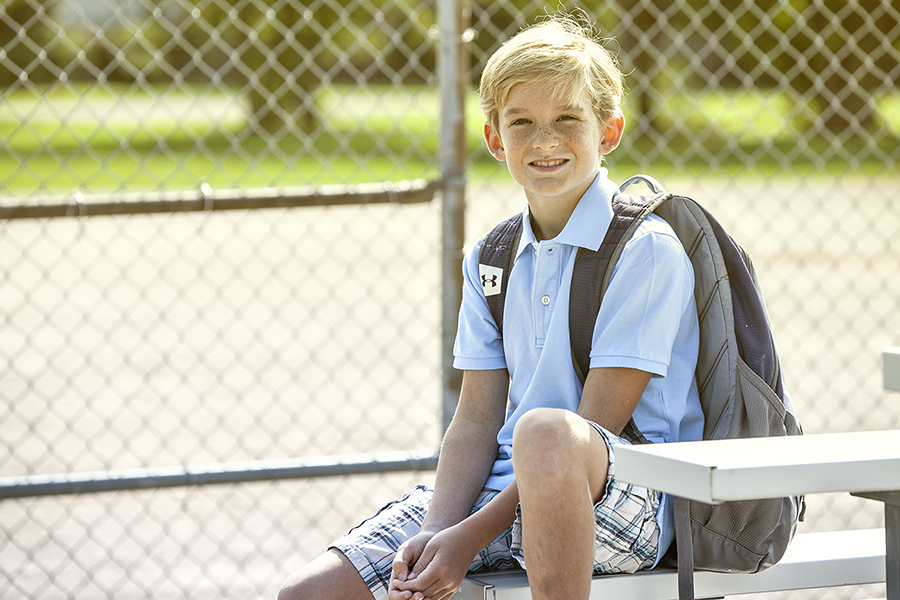 Boy sitting in the park with his sports bag