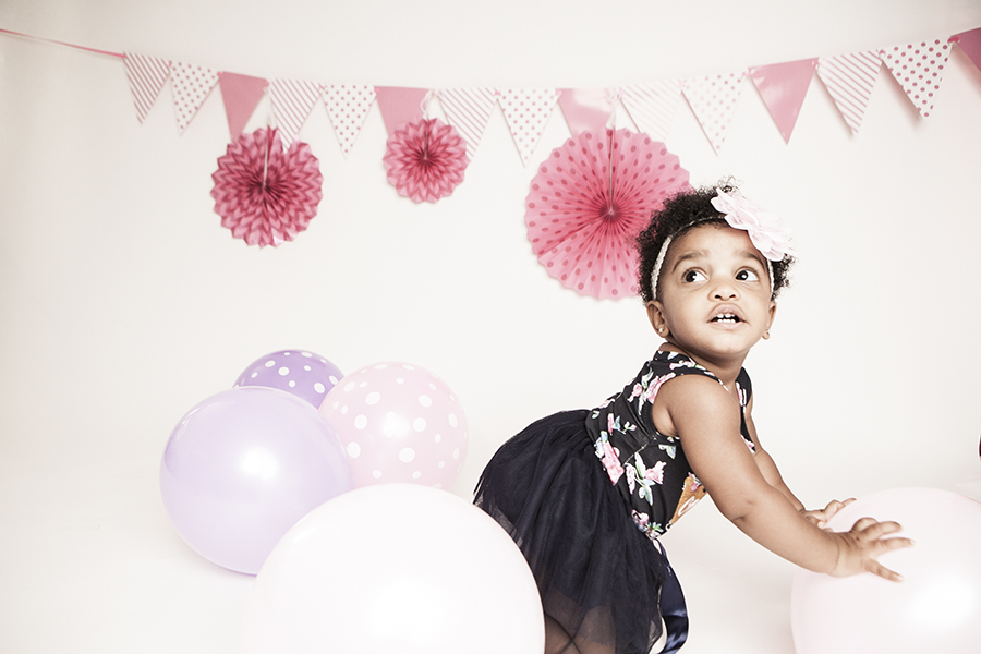Baby smiling at the camera during a cake smash photoshoot