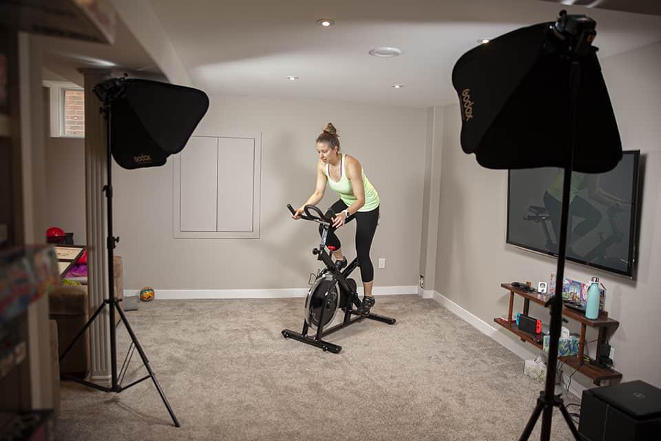 Health Coach riding an exercise bike at a Brooklin Branding photoshoot