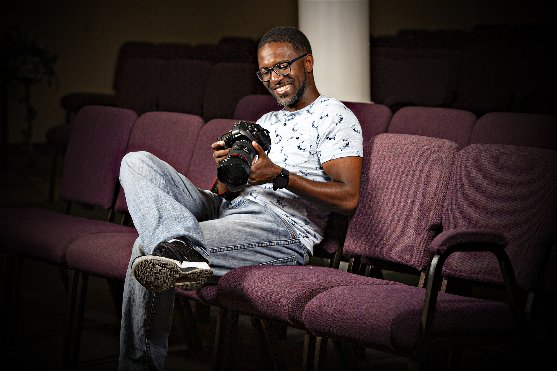 Sheldon Isaac smiling at a photo on his camera in Scarborough