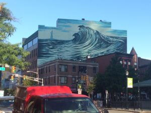 Mural painting of a wave on the side of a building.