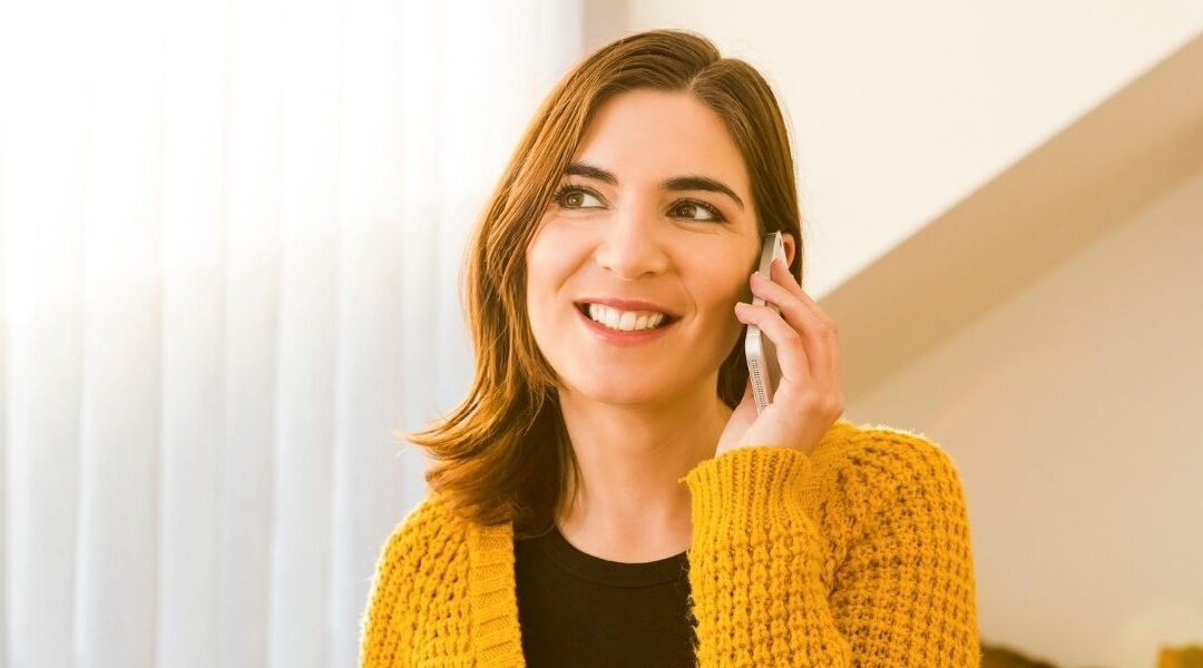 A girl smiling while making a free online call.