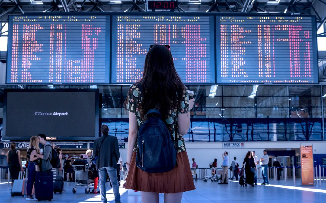 A woman traveling alone standing in an airport.