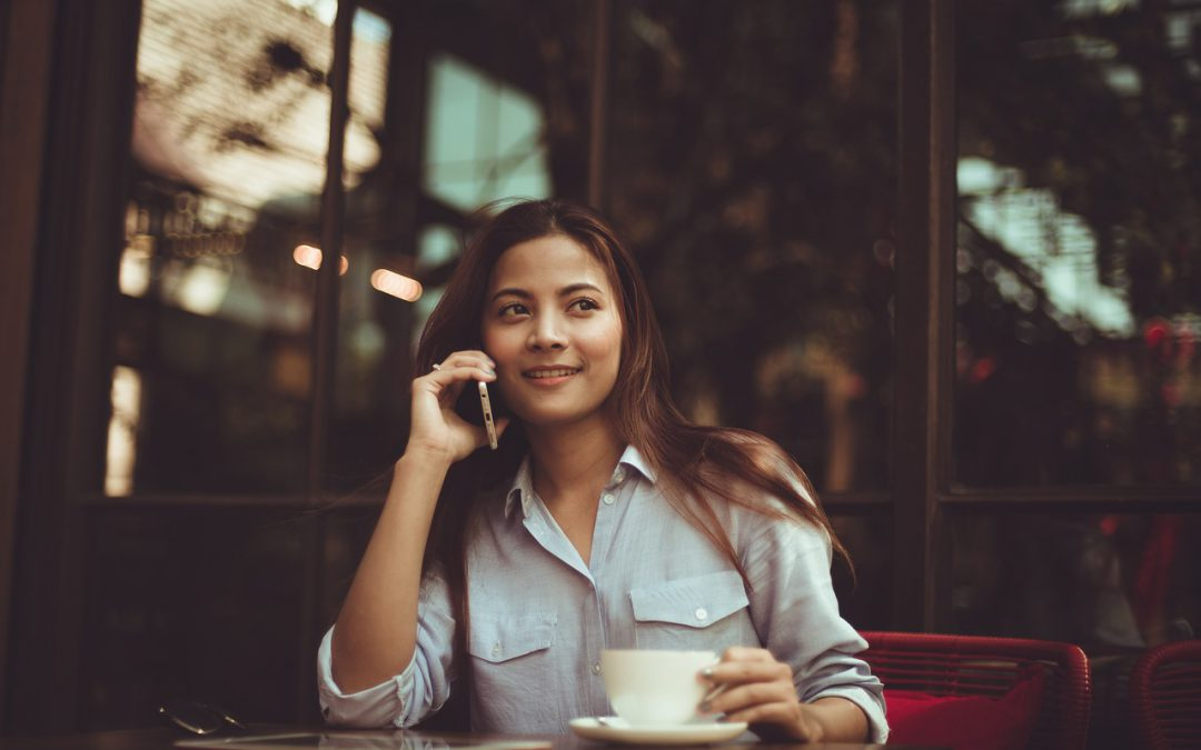 woman calling on phone while holding a cup of coffee